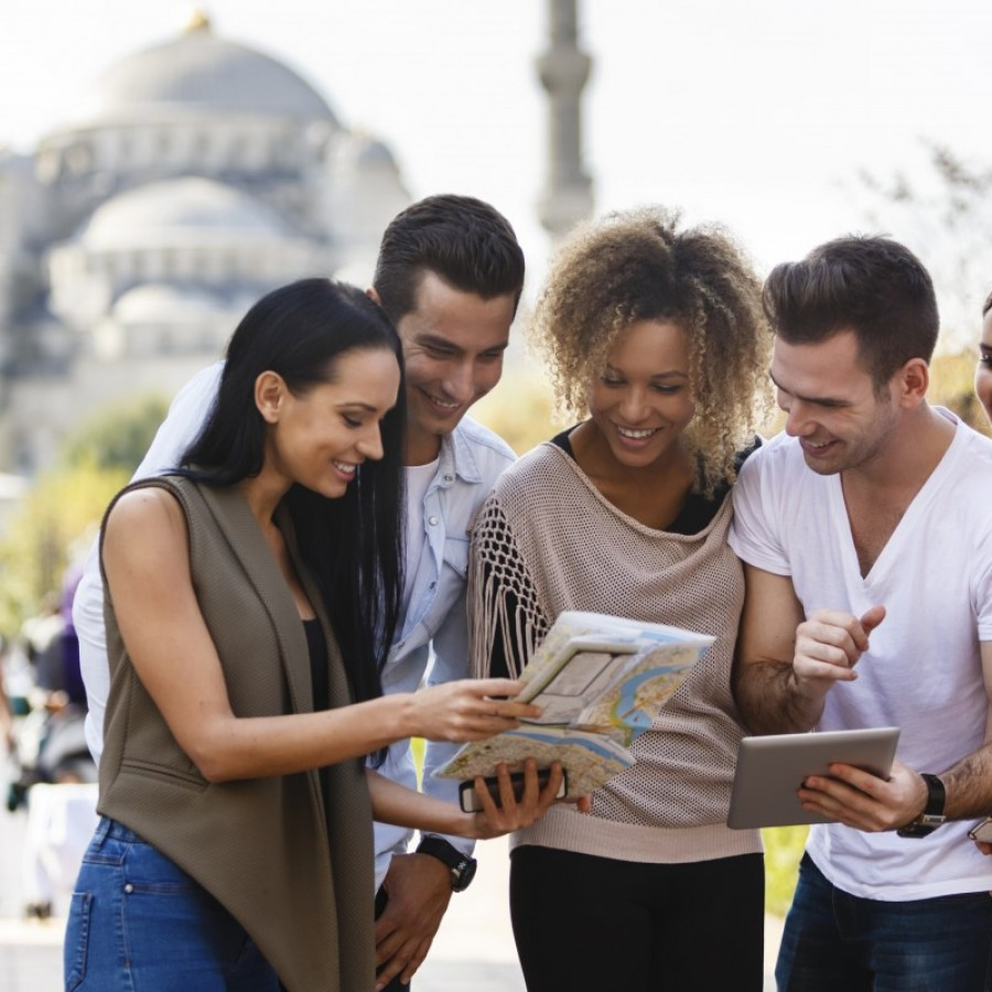 Group of happy tourists with digital tablet and a map in Sultanahmet district in Istanbul, Turkey. Blue mosque is in the background.
